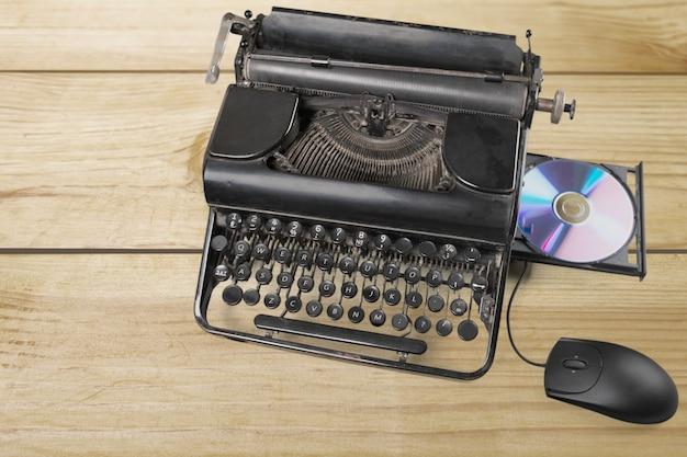 Máquina de escrever antiga com disco de computador e mouse no fundo