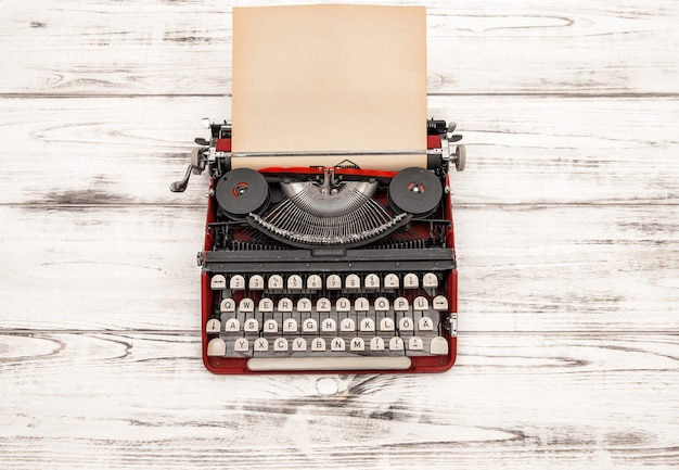Máquina de escrever antiga com página de papel texturizado sujo na mesa de madeira. estilo vintage natureza morta. letras alemãs