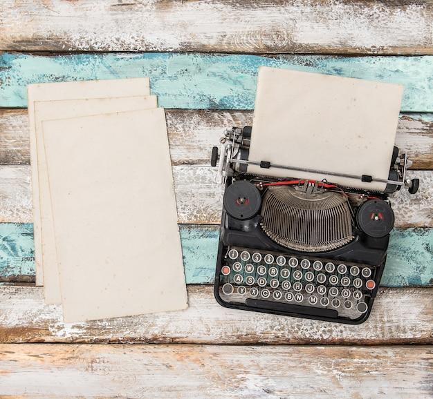 Máquina de escrever antiga e folhas de papel usadas na mesa de madeira. flat lay still life
