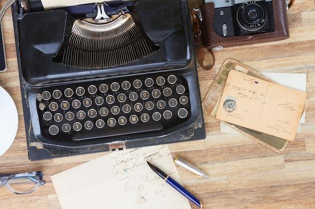 Máquina de escrever antiga preta com livros e correspondências antigas na mesa de madeira