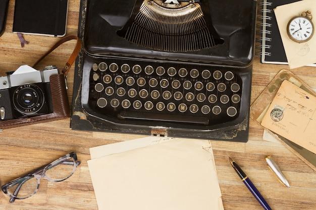 Máquina de escrever antiga preta com suprimentos na mesa de madeira, copie o espaço em papel envelhecido
