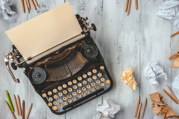 Máquina de escrever com papel e lápis