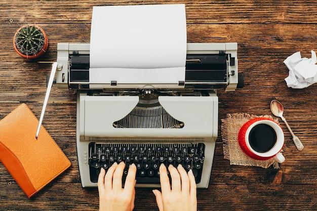 Máquina de escrever com vista superior das mãos de mulher.