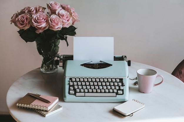 Máquina de escrever de hortelã retrô por rosas cor de rosa