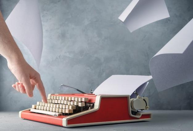 Máquina de escrever em cima da mesa com folhas de papel