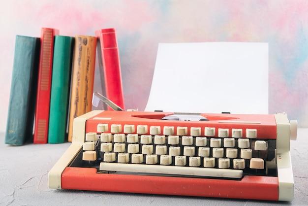 Máquina de escrever em cima da mesa com livros