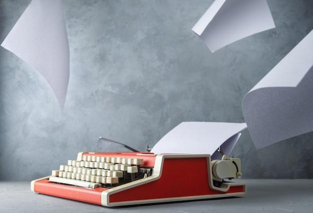 Máquina de escrever em cima da mesa e folhas de papel