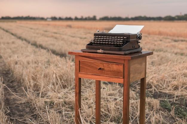 Máquina de escrever em uma mesa de cabeceira de noz em um campo de trigo ao pôr do sol