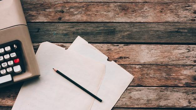 Máquina de escrever, lápis e papel com fundo de madeira. literatura, oficina de escrita criativa e jornalismo.