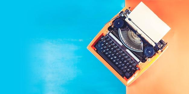 Máquina de escrever laranja vintage e folhas de papel