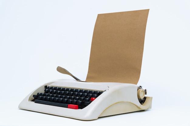 Máquina de escrever retro com a folha do papel em branco no branco.