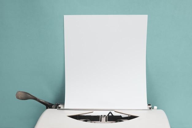 Máquina de escrever retro com a folha do papel vazio no fundo azul da parede da parte dianteira de madeira branca da tabela com espaço da cópia.