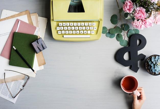 Máquina de escrever retrô com a mão segurando a xícara de chá em fundo cinza