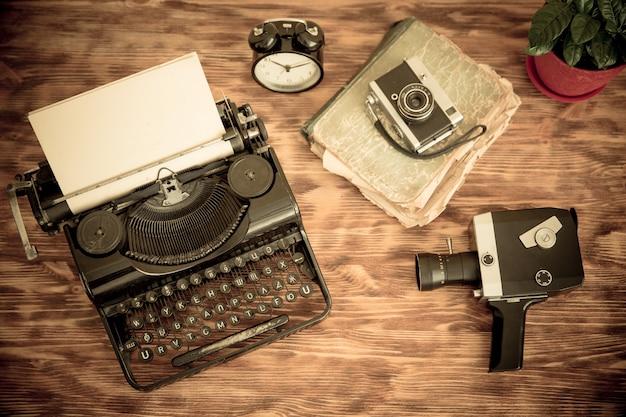 Máquina de escrever retrô com papel em branco sobre fundo de madeira. vista do topo