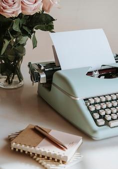 Máquina de escrever retro hortelã por rosas cor de rosa Foto Premium