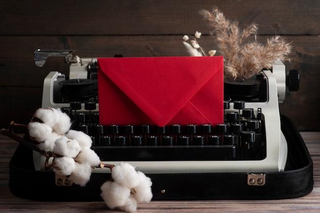 Máquina de escrever russa close-up e flores secas com envelope vermelho