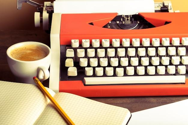 Máquina de escrever velha com papel e café no fundo