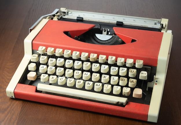 Máquina de escrever vermelha em cima da mesa