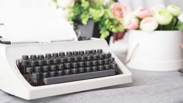 Máquina de escrever vintage com papel. tecnologia de máquina retro - superfície branca com flores