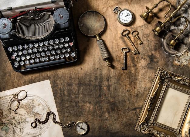 Máquina de escrever vintage e acessórios de escritório antigos na mesa de madeira. natureza morta nostálgica