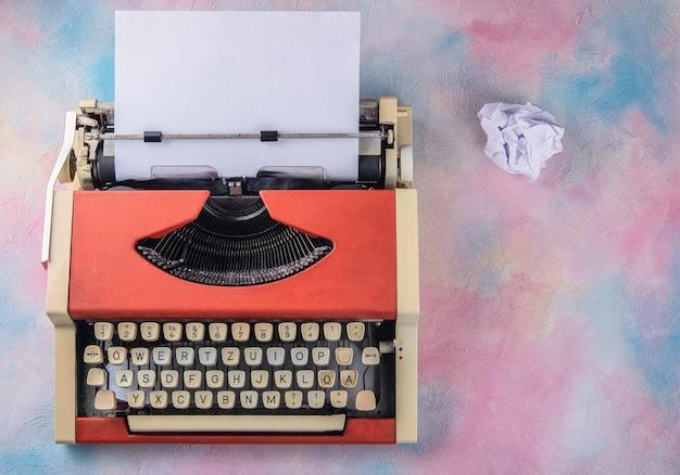 Máquina de escrever vintage e folha amassada na vista superior da mesa