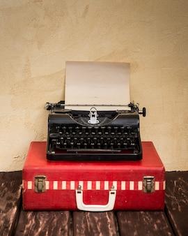 Máquina de escrever vintage e mala vermelha clássica. conceito de viagens