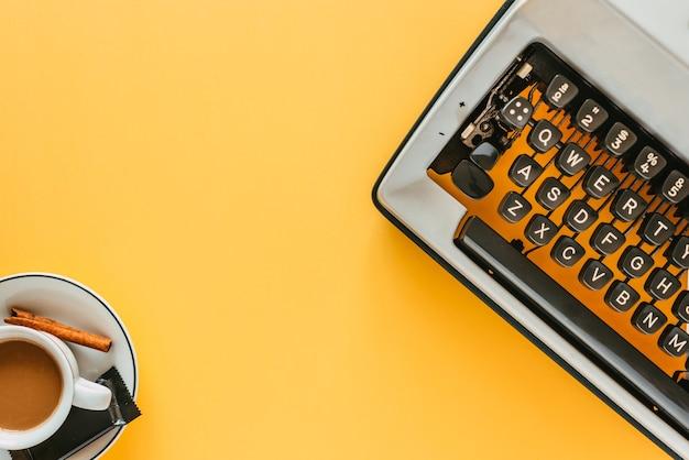 Máquina de escrever vintage e xícara de café em um fundo amarelo esperando por você para escrever seu melhor romance.