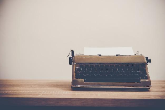 Máquina de escrever vintage em mesa de madeira.