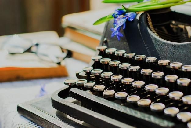 Máquina de escrever vintage, livros antigos na mesa