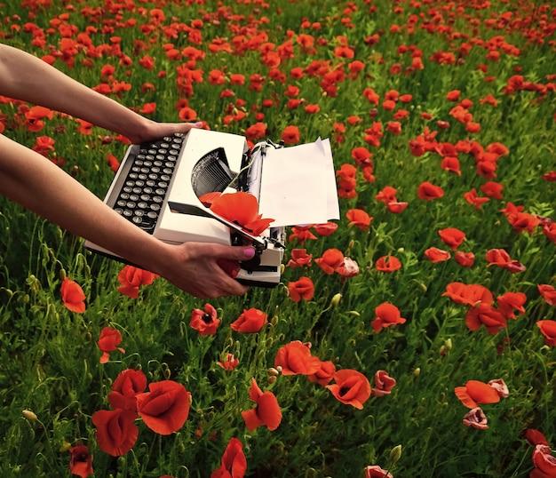 Máquina de escrever vintage na mão educação negócios gramática papoula nova tecnologia dia da lembrança journalis ...