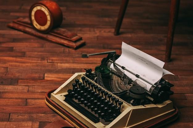 Máquina de escrever vintage para imprimir folha branca de papel fundo de madeira invenção retrô