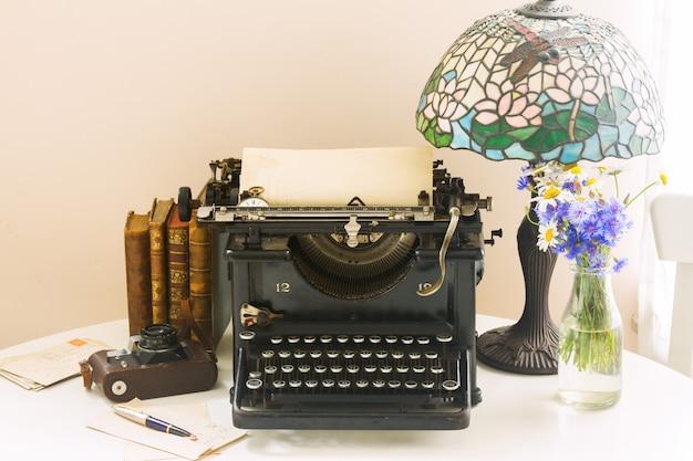Máquina de escrever vintage preta com livros na mesa de madeira e lâmpada art nuveau