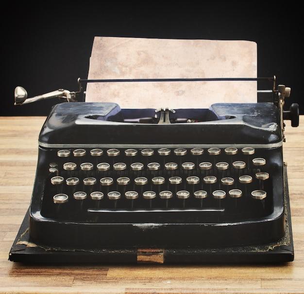 Máquina de escrever vintage preta com página em branco vazia na mesa de madeira, retro tonificada