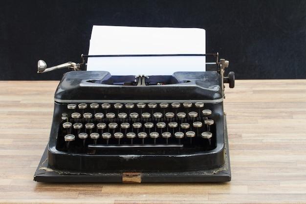 Máquina de escrever vintage preta com página em branco vazia na mesa de madeira