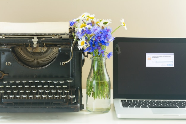 Máquina de escrever vintage preta e laptop moderno na mesa de madeira