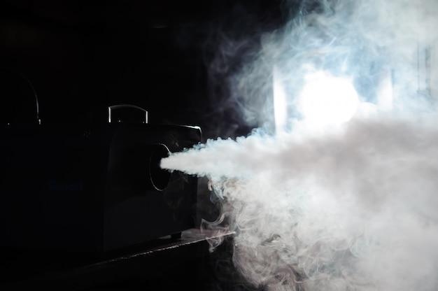 Máquina de fumaça em luzes de ação na fumaça