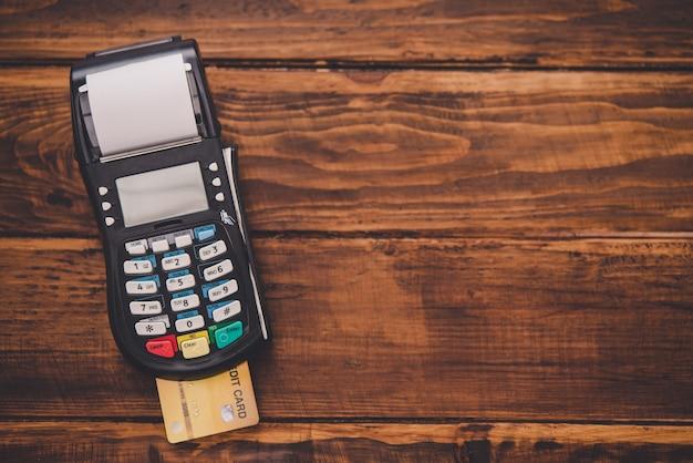 Máquina de furto de cartão de crédito de vista superior colocada em um piso de madeira, significando pagamento por cartão de crédito