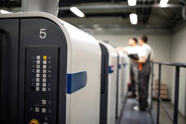 Máquina de impressão offset moderna e operadores em processo de controle uniforme de trabalho