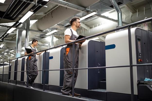 Máquina de impressão offset moderna e operadores trabalhando no processo de controle uniforme de impressão