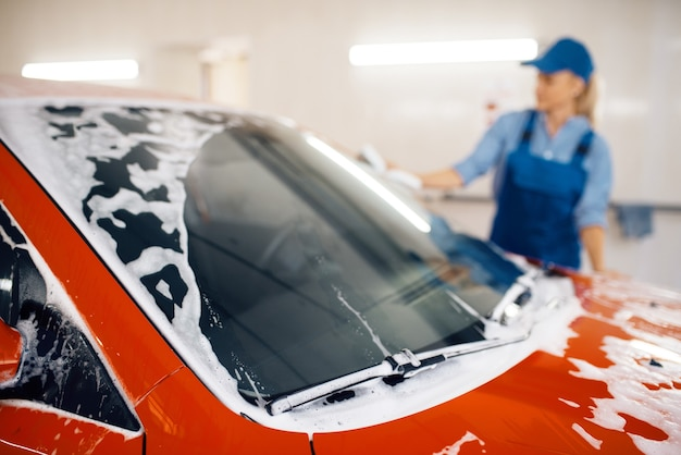 Máquina de lavar fêmea com esponja limpa o para-brisa do automóvel