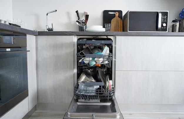 Máquina de lavar louça, aberta e carregada com pratos na cozinha, após a lavagem.