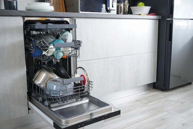 Máquina de lavar louça, aberta e carregada com pratos na cozinha