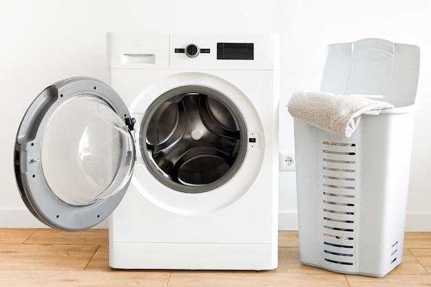 Máquina de lavar roupa com cesto de roupa suja na lavanderia de casa