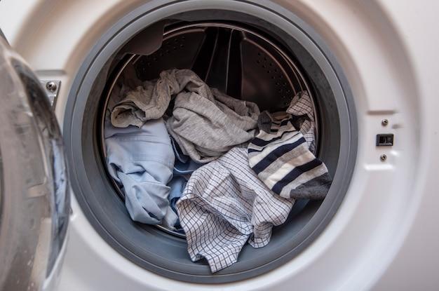 Máquina de lavar roupa com porta aberta e roupas sujas antes de lavar, máquina cheia de roupas sujas