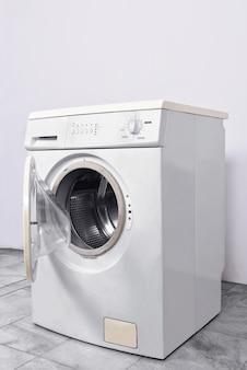 Máquina de lavar roupa com porta aberta em casa