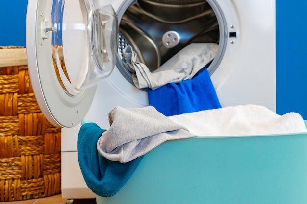 Máquina de lavar roupa com roupa na parede azul