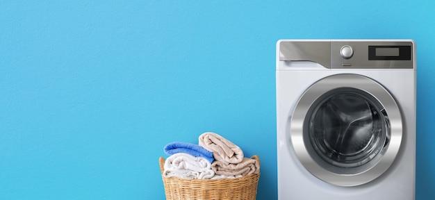 Máquina de lavar roupa com roupa perto de toalhas de banho limpas em uma cesta de vime no fundo da parede azul