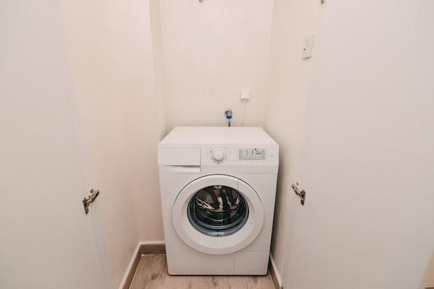 Máquina de lavar roupa no apartamento perto da arrecadação para lavar roupa