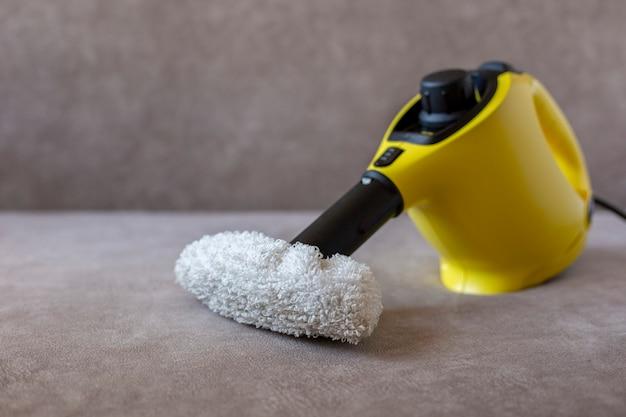Máquina de limpeza a vapor amarela com toalha de rosto em um sofá marrom, vista de cima