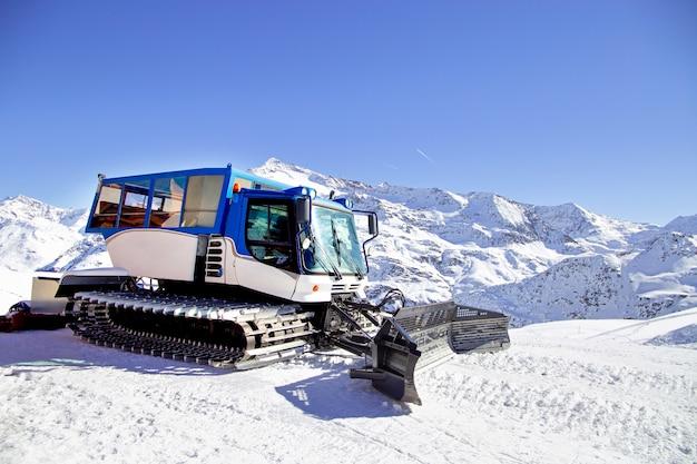 Máquina de limpeza de neve na colina de neve pronta para preparações de esqui nos alpes, estância de esqui na europa